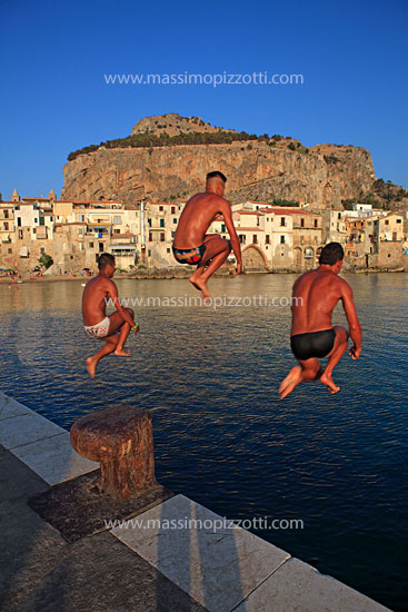 Italy, Cefalù, Guys dipping into the sea